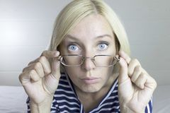 Emotional beautiful cute blond woman wearing glasses and holding it by hands, light gray background. Facial expressions. stock image