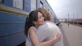 Emotional beautiful girl embrace guy and laughs near railway carriage on Train Station after separation. Emotional beautiful girl embrace guy and laughs near stock video