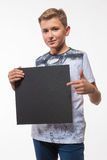 Emotional blond boy in a white shirt with a gray sheet of paper for notes Stock Photo
