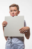 Emotional blond boy in a white shirt with a gray sheet of paper for notes Royalty Free Stock Image