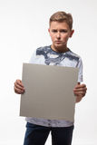 Emotional blond boy in a white shirt with a gray sheet of paper for notes Stock Image