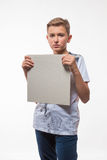 Emotional blond boy in a white shirt with a gray sheet of paper for notes Stock Photography