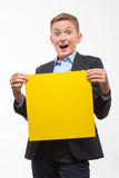Emotional blond teenager boy in a suit with a yellow sheet of paper for notes. On a white background Stock Photography