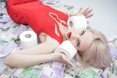 An emotional blonde girl in a red dress is lying on scattered money with toilet paper. a rich person during an epidemic is ready