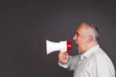Emotional boss with megaphone. Sideview of emotional boss with megaphone over dark background Royalty Free Stock Photos