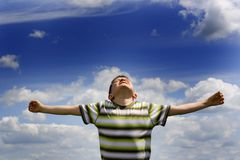 Emotional Boy. Elated boy with arms stretched out to his sides, and face turned upward.  Blue sky and clouds background Royalty Free Stock Image