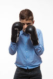 Emotional boy brunette in a blue shirt with boxing gloves in hands Royalty Free Stock Image