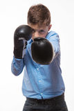 Emotional boy brunette in a blue shirt with boxing gloves in hands Royalty Free Stock Photography