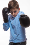 Emotional boy brunette in a blue shirt with boxing gloves in hands Royalty Free Stock Photos