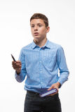 Emotional boy brunette in a blue shirt with a diary and a pen in hand Royalty Free Stock Photo
