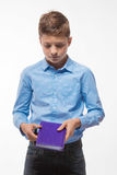 Emotional boy brunette in a blue shirt with a diary and a pen in hand Royalty Free Stock Photos