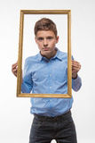 Emotional boy brunette in a blue shirt with a picture frame in the hands Royalty Free Stock Image