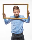 Emotional boy brunette in a blue shirt with a picture frame in the hands Stock Image