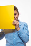 Emotional boy brunette in a blue shirt with yellow sheet of paper for notes. On a white background Royalty Free Stock Photo