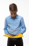Emotional boy brunette in a blue shirt with yellow sheet of paper for notes. On a white background Stock Photo