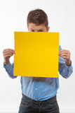 Emotional boy brunette in a blue shirt with yellow sheet of paper for notes. On a white background Stock Photography