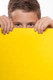 Emotional boy brunette in a blue shirt with yellow sheet of paper for notes. On a white background Stock Images