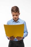 Emotional boy brunette in a blue shirt with yellow sheet of paper for notes. On a white background Royalty Free Stock Photography