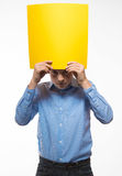 Emotional boy brunette in a blue shirt with yellow sheet of paper for notes Royalty Free Stock Images