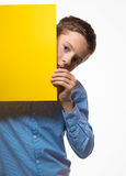 Emotional boy brunette in a blue shirt with yellow sheet of paper for notes. On a white background Royalty Free Stock Photos