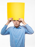 Emotional boy brunette in a blue shirt with yellow sheet of paper for notes. On a white background Stock Photos
