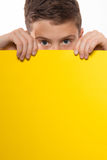 Emotional boy brunette in a blue shirt with yellow sheet of paper for notes. On a white background Royalty Free Stock Images