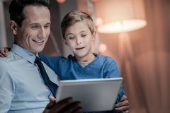Emotional boy embracing his father. Watching video. Cheerful male person holding tablet in right hand, spending time with son Royalty Free Stock Image