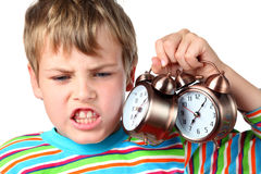 Emotional boy holds two alarms. Little emotional blond boy in striped shirt holds two alarms near head stock photo
