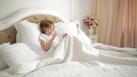 Emotional Boy is Playing in Video Games Using Tablet. Portrait of Child with Electronic Gadget in the Bed. Emotional Boy is Playing in Games Using Tablet stock footage