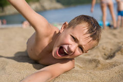 Emotional boy relaxing on the beach. Stock Photo