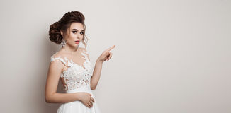 Emotional bride in white dress shocked looking at camera with opened mouth. Beautiful brunette woman with stylish haircut posing, Royalty Free Stock Images