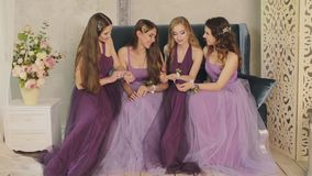 Emotional bridesmaids look at the boutonniere on their hands, talking and laughing during the morning of the bride in a stock video