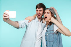 Emotional brother and sister make selfie by mobile phone royalty free stock photography