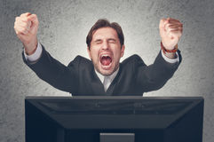 Emotional businesman rejoices win at computer. Emotional young businesman rejoices win at the computer Stock Photos