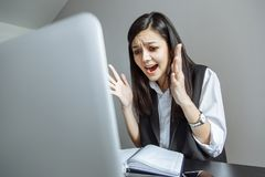 Emotional business lady shouting at her laptop. Hard stressful workday in the office royalty free stock image