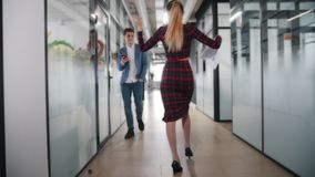 An emotional business woman dancing in office corridor across her colleagues. Colleagues turn around on her