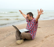 Emotional  businessman with laptop on the beach Stock Images