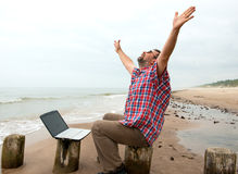 Emotional  businessman with laptop on the beach Stock Photo