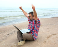 Emotional  businessman with laptop on the beach Stock Photography