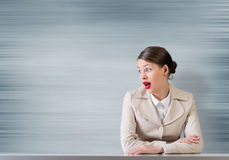 Emotional businesswoman. Pretty astonished businesswoman with opened mouth sitting at table Royalty Free Stock Photo