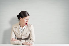 Emotional businesswoman. Pretty astonished businesswoman with opened mouth sitting at table Royalty Free Stock Image
