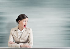 Emotional businesswoman. Pretty astonished businesswoman with opened mouth sitting at table Stock Image