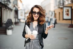 Emotional busy brunette at street talking on call phone.