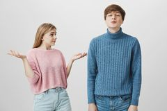 Emotional caucasian couple. Young male dressed in blue sweater pouts lips, sends kisses to camera, while his girlfriend Stock Images