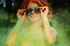 Emotional caucasian model wearing sunglasses, posing in a cloud. Emotional caucasian woman wearing sunglasses, posing in a cloud of green Gulal paint royalty free stock image