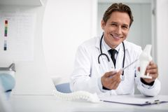 Friendly general practitioner holding knee model and smiling royalty free stock photos