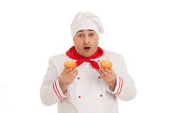 Emotional chef holding two muffins wearing red and white uniform Royalty Free Stock Photography