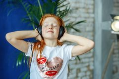 An emotional child listens to songs in the headphones and dances. The concept is childhood, lifestyle, music, singing, listening, hobbies Royalty Free Stock Image