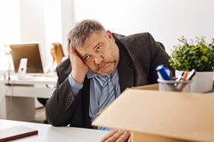Emotional chubby guy being sad about his dismissal. Awful situation. Overwhelmed sorrowful pudgy men sitting at his desk and thinking about what he doing wrong royalty free stock photo