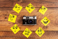 Emotional circle. Close-up of retro camera surrounding by adhesive notes with drawings on them royalty free stock photos